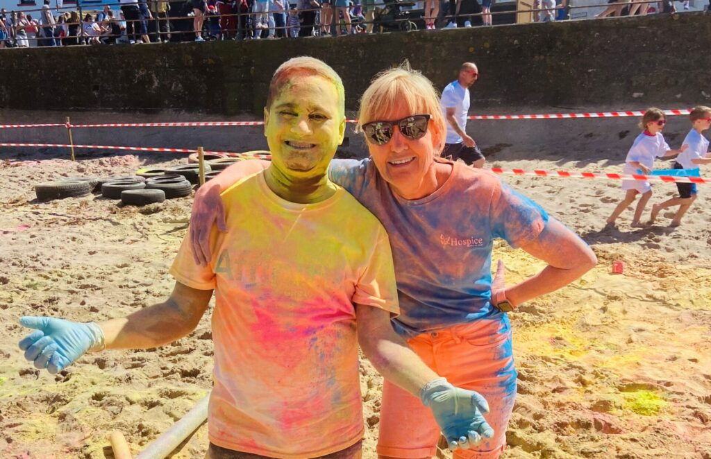 2 people covered in colourful powder on the beach