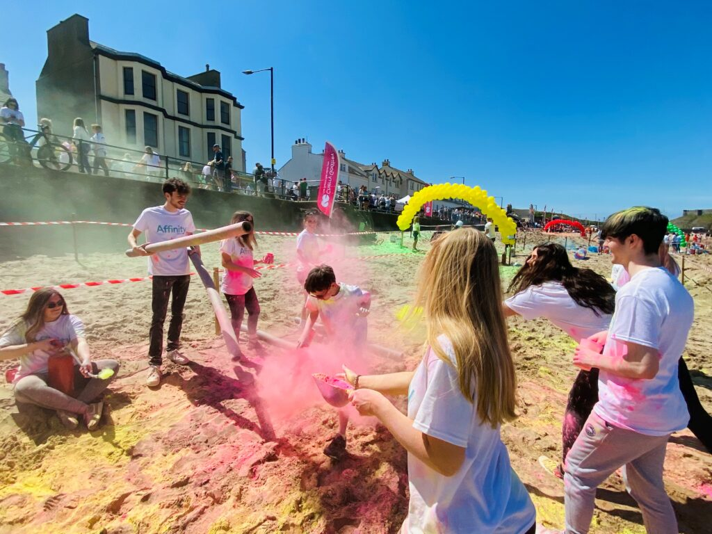 Affinity members throw coloured powder at the colour run event in Peel