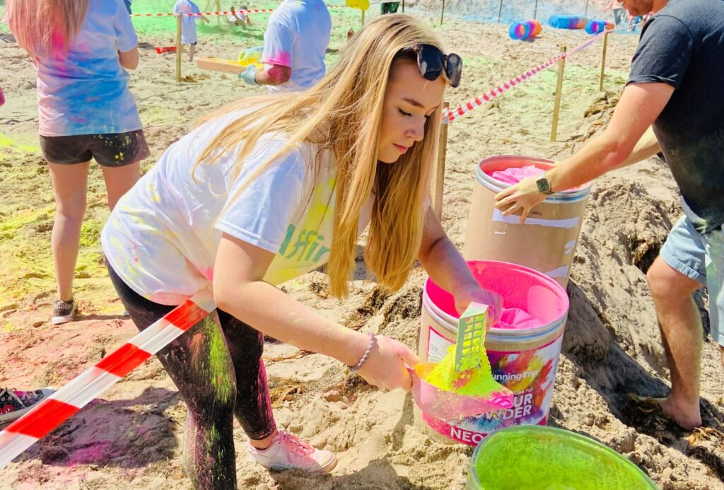Affinity team member prepares a scoop of coloured powder for the colour run event
